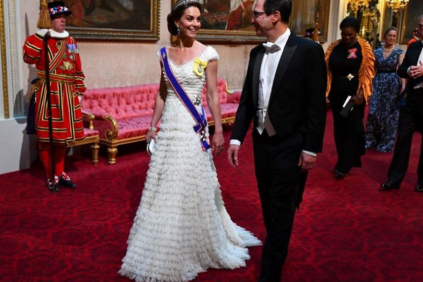 The Duchess of Cambridge Catherine Middleton walks with US Treasury Secretary Steven Mnuchin as they arrive to the state banquet on June 3, 2019.