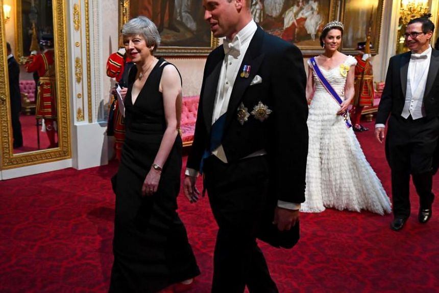 British Prime Minister Theresa May walks with Prince William as they arrive for the state banquet in the ballroom at Buckingham Palace on June 3, 2019.