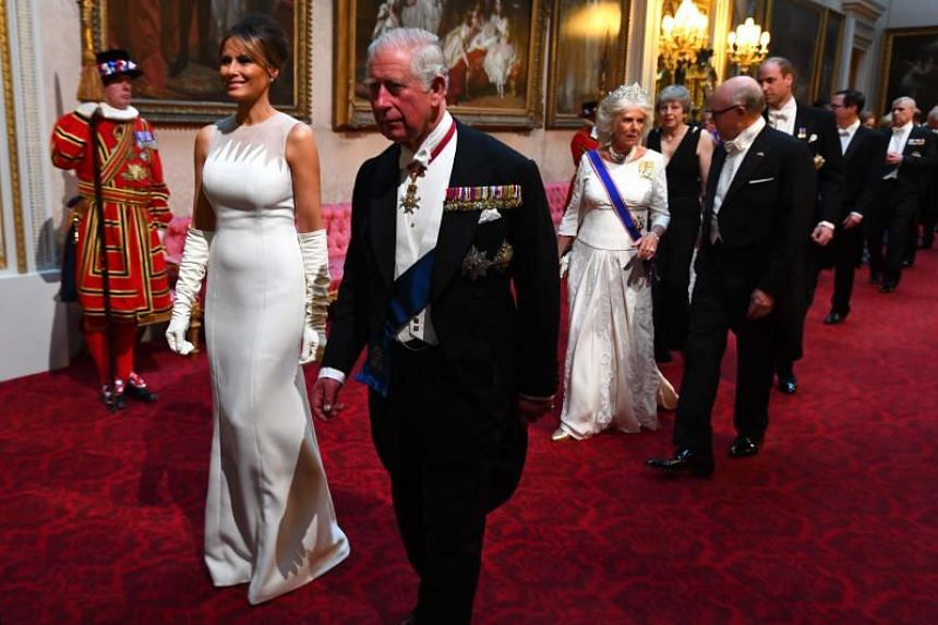 Britain's Prince Charles, Prince of Wales, walks with US First Lady Melania Trump. They are followed by Britain's Camilla, Duchess of Cornwall, and US Ambassador to the UK Woody Johnson.
