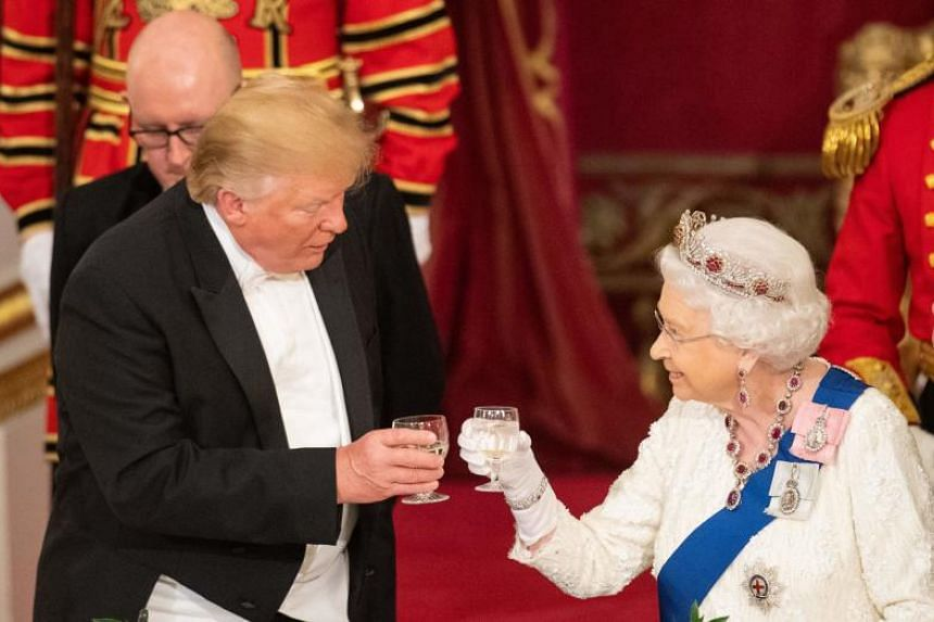 Britain's Queen Elizabeth raises a glass in a toast with US President Donald Trump during the state banquet on June 3, 2019.