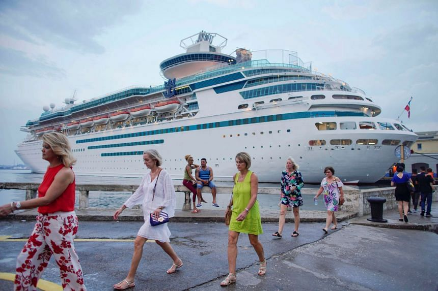 Tourists walk next to the Majesty of the Seas cruise ship, in Havana, Cuba, May 6, 2019.