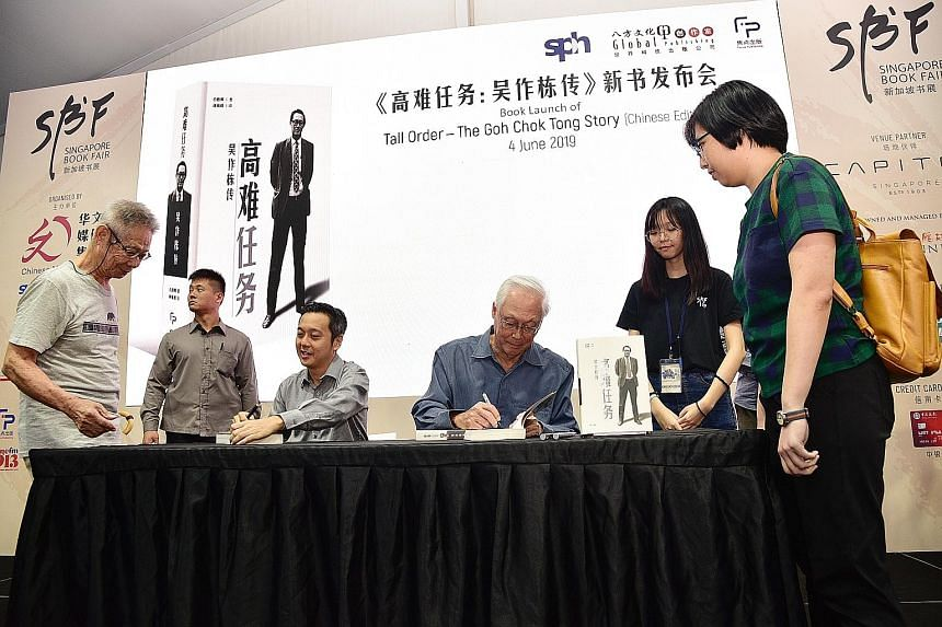 Emeritus Senior Minister Goh Chok Tong signing his book, Tall Order: The Goh Chok Tong Story, for a member of the public at the Singapore Book Fair 2019 yesterday. With him was Mr Peh Shing Huei, who wrote the biography.