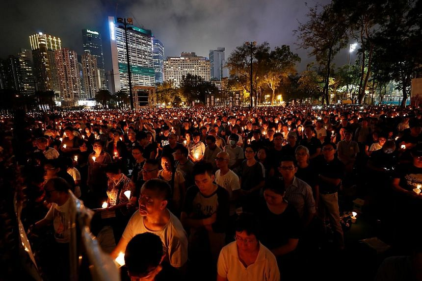 Witnesses of the Tiananmen Square crackdown standing before an inflatable tank sculpture at Chiang Kai-shek Memorial Hall in Taipei yesterday. Activists lighting candles at the Chinese Consulate in the Philippine capital Manila yesterday during a com