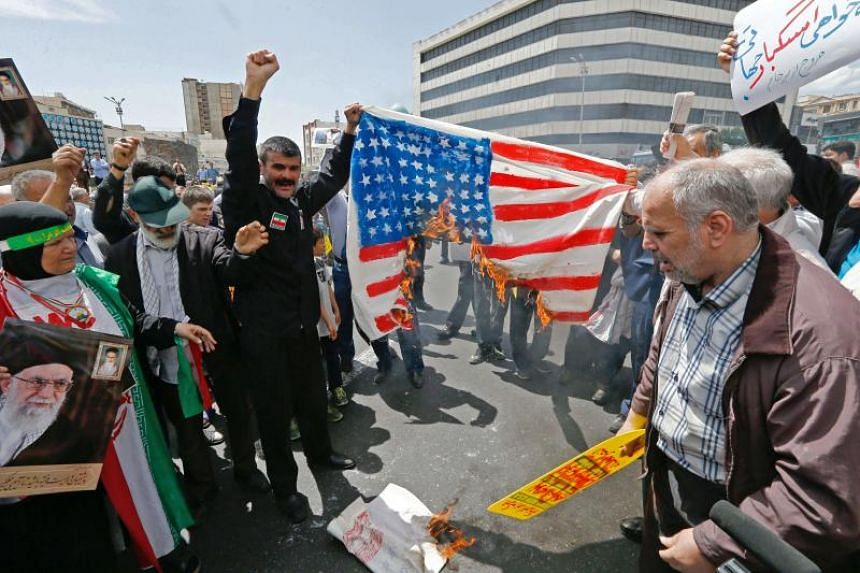 """Demonstrators burn a makeshift US flag during a rally in Teheran, on May 10 2019. US President Donald Trump said there's """"always a chance"""" of the US taking military action in Iran amid heightened tension between the two countries."""