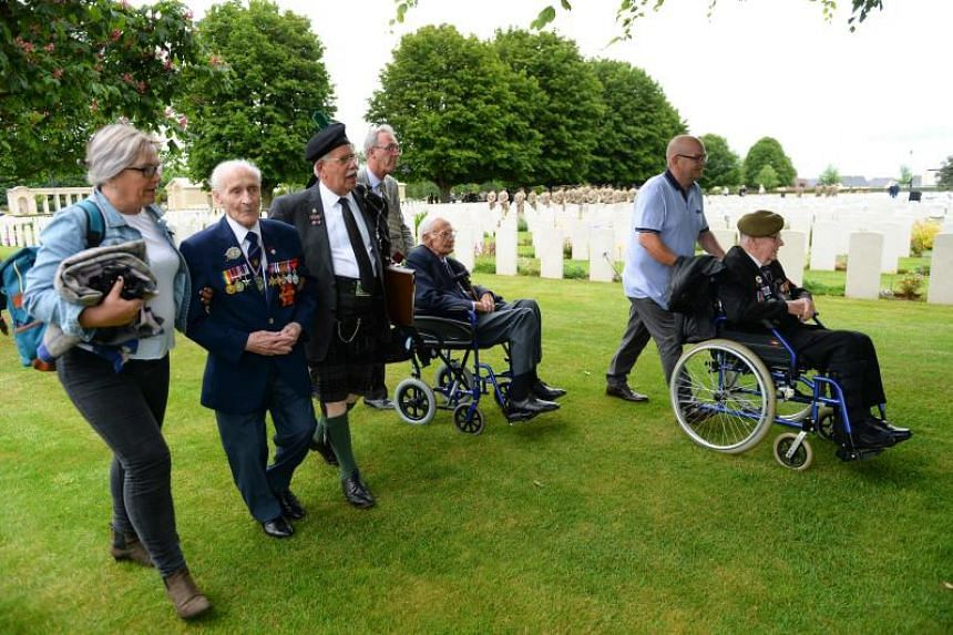 British veterans, Ernie Covill (second from left), John Summerson (centre) and Sid Barnes (right) arrive at The Normandy British Cemetery in Bayeux, France, on June 5, 2019, as part of events for the 75th anniversary of D-Day.