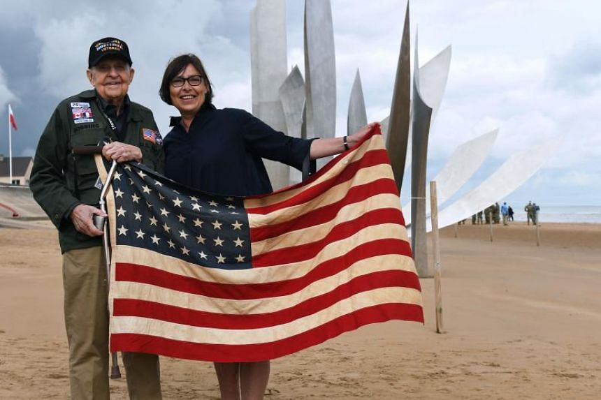 US veteran KT Robbins with a tourist on Omaha Beach in Normandy, France, on June 5, 2019, as part of commemorations marking the 75th anniversary of of D-Day.