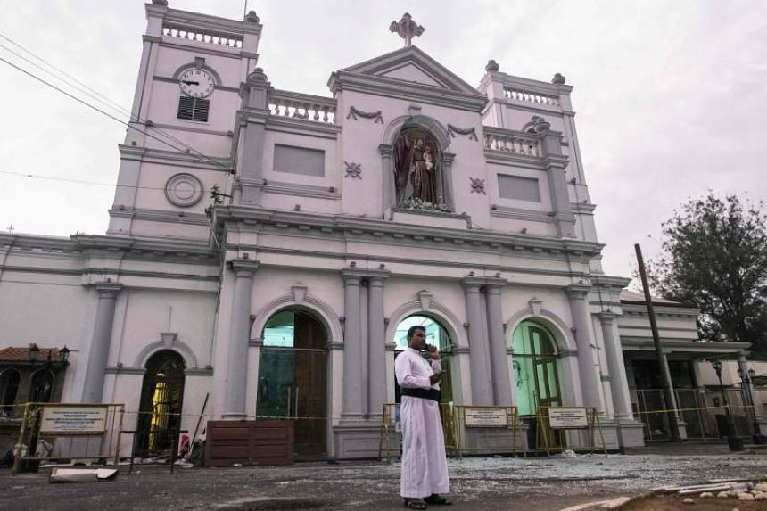 A priest speaks on the phone outside St Anthony's Shrine in Colombo on April 26, 2019, following a series of bomb blasts targeting churches and luxury hotels on Easter Sunday in Sri Lanka.