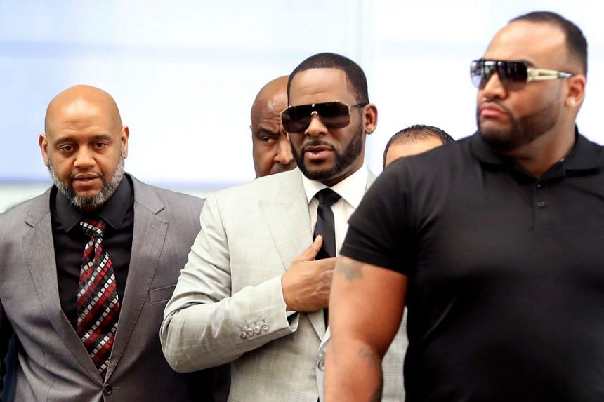 R. Kelly (centre) heads into court to face 11 new counts of criminal sexual abuse, in Chicago, Illinois.