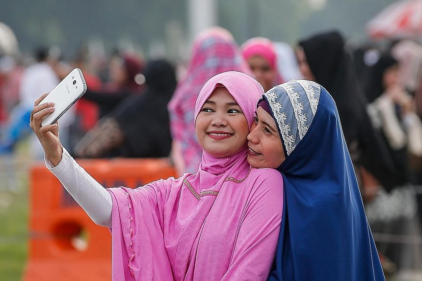A Buddhist woman giving a rose to a Muslim boy after his prayers yesterday in Than Lyin on the outskirts of Yangon, Myanmar. Children playing with balloons during the Eid al-Fitr celebrations yesterday at Puputan Garden in Denpasar, Bali in Indonesia