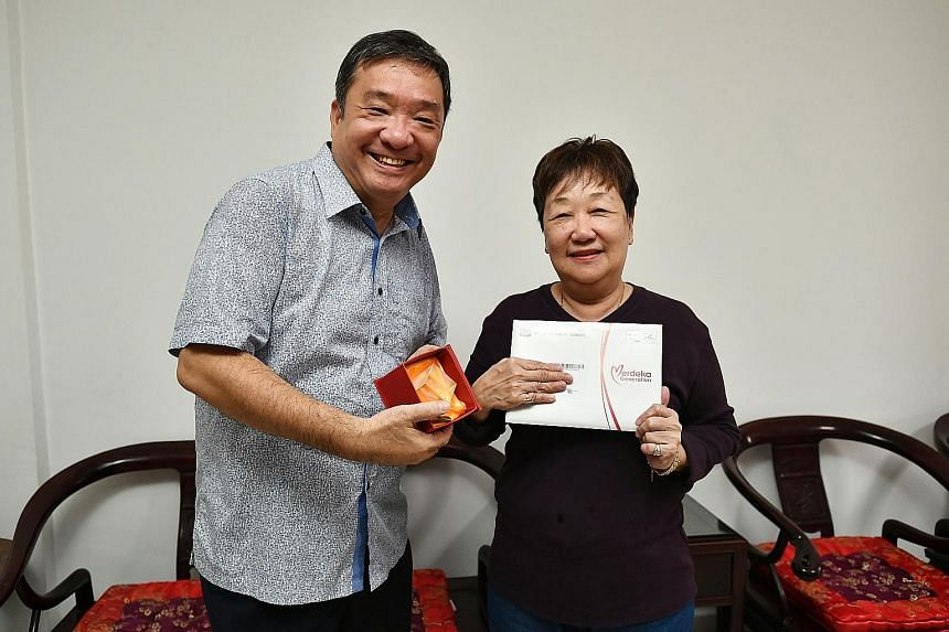 Potong Pasir MP Sitoh Yih Pin giving out Merdeka Generation Package items to Madam Thng Bee Keow, 69, a retired beautician, on Monday. He will make his way through 59 blocks in the next three weeks to deliver the packages by hand. ST PHOTO: LIM YAOHU