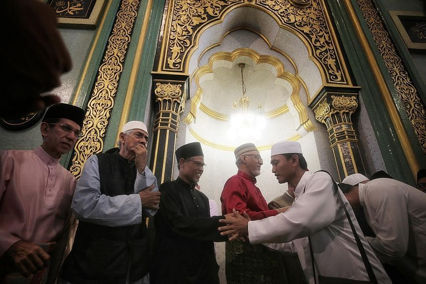 Minister-in-charge of Muslim Affairs Masagos Zulkifli (third from left) greeting congregants together with (from left) Islamic Religious Council of Singapore president Mohammad Alami Musa, the mosque's chairman Mohamed Salleh Patail, and Mr Mohamed A