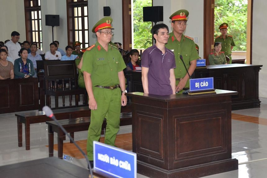 Vietnamese Facebook user Nguyen Ngoc Anh stands between policemen during his trial at a court in Ben Tre province, Vietnam, on June 6, 2019.