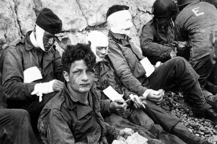 American troops of the 16th Infantry Regiment, injured while storming Omaha Beach, waiting to be evacuated to a field hospital, in Normandy, France, on June 6, 1944.