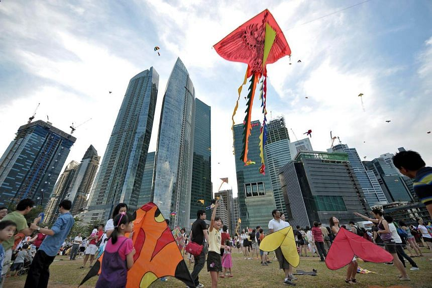 Families flying kites in Marina Bay near Singapore's central business district.