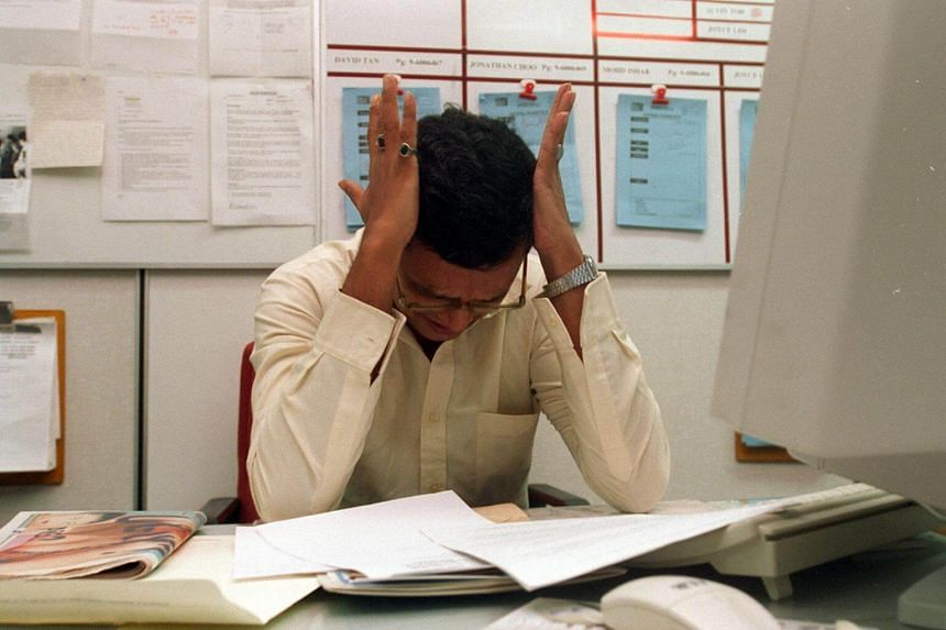 Posed photo of a man stressed at work.