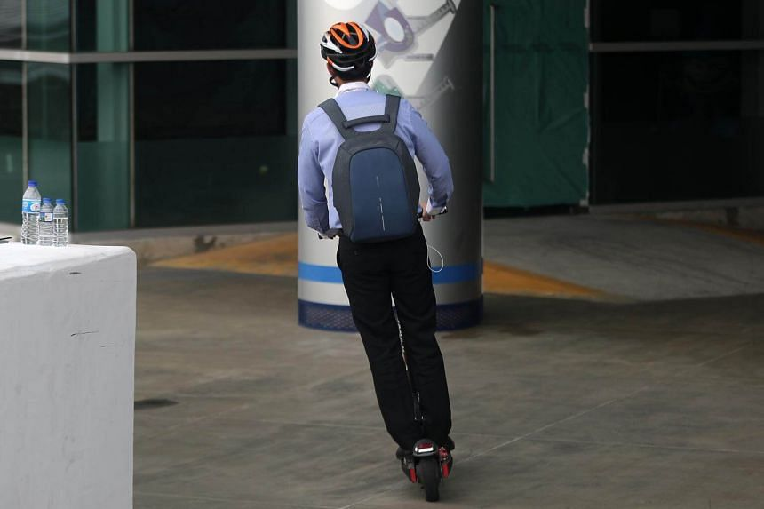 A man with a safety helmet riding an electric scooter at Marina Barrage.