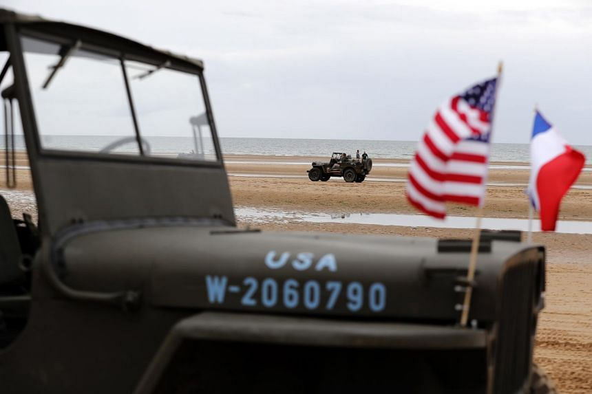 History enthusiasts drive a Willy's jeep in Omaha Beach, France, on June 5, 2019.