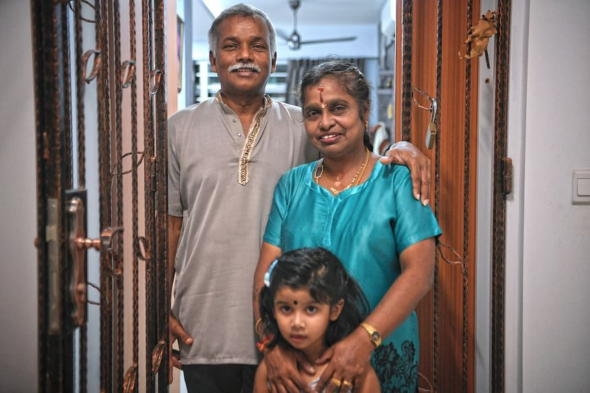 Madam Senthamizhselvi, 55, with husband Govindasamy Shanmugam, 59, and their granddaughter, Kayal Gobiraj, three, at the couple's purchased flat in Block 182A Woodlands Street 13, the only HDB block thus far with both rental and purchased units. She