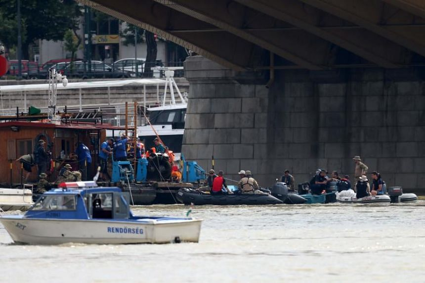 Divers prepare themselves at the position of the sunk Hungarian riverboat as the search for its missing passengers continues on the Danube river in Budapest, on June 6, 2019.