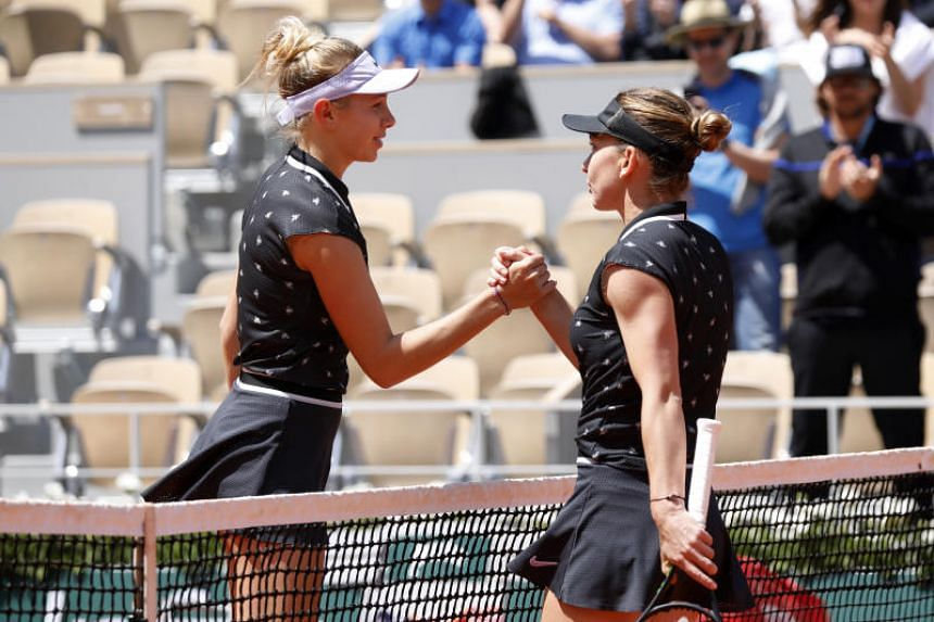 Simona Halep (right) was knocked out of the French Open 6-2, 6-4 by 17-year-old American Amanda Anisimova.