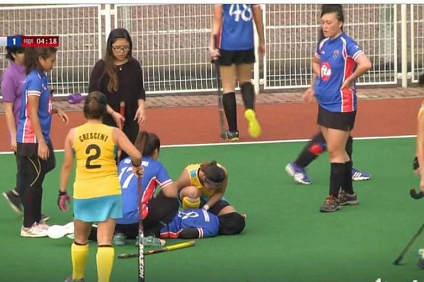 Miss Siti Nur Raihanah Waled (centre) suffered a head injury after colliding with an opponent during a hockey match.