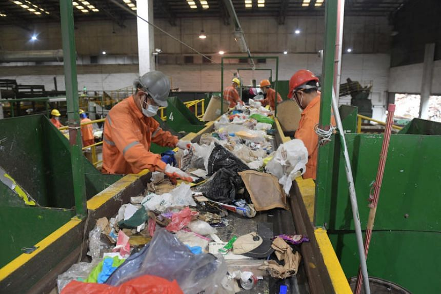 Workers sort materials at SembWaste's Materials Recycling Facility on June 6, 2019.