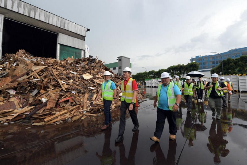 NTUC secretary-general Ng Chee Meng (in red) tours SembWaste's Materials Recycling Facility on June 6, 2019.