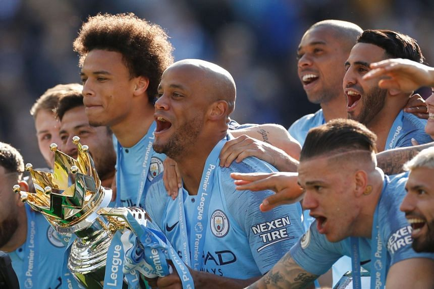 Manchester City's Vincent Kompany lifts the trophy as the team celebrates winning the Premier League in 2019.