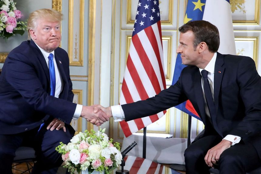 Trump and Macron shake hands during a meeting on the sidelines of D-Day commemorations.