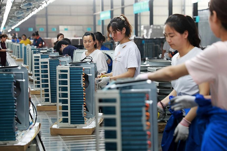 Workers at a factory manufacturing air-conditioners in Huaibei, Anhui province, in China. The 11-page research report by China's Commerce Ministry notes how bilateral trade in goods has jumped 252 times to reach US$633.5 billion (S$864 billion) since