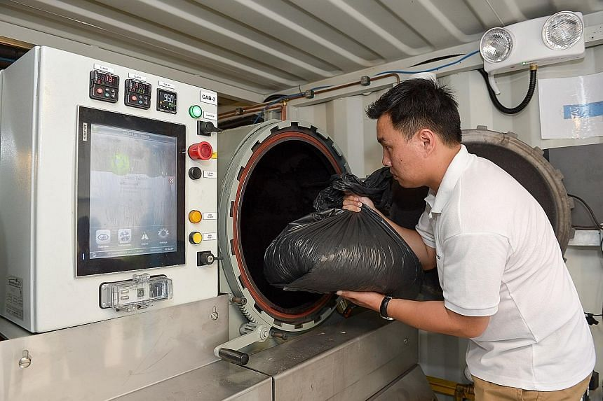 Mr Dex Ng, assistant director for conservation and environmental sustainability at Gardens by the Bay, demonstrating the disposal of trash into the gasification system. The system, created by SP Group, began operating last month and will run as a pil