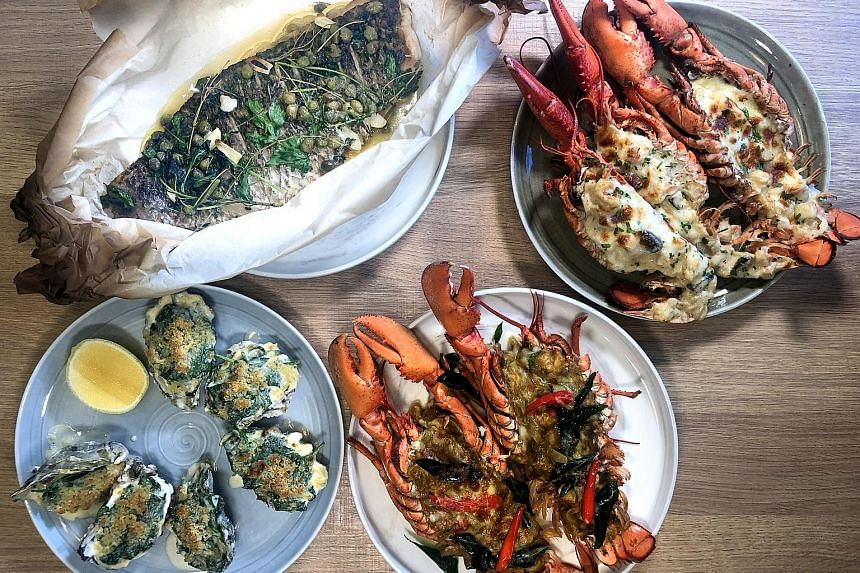 (Clockwise from top left) Baked Whole Seabass with burnt butter and capers, Lobster Thermidor, Curry Lobster and Oyster Rockefeller are highlights of the Father's Day Brunch at Sky22 at Courtyard by Marriott Singapore Novena. The grilled ox tongue at