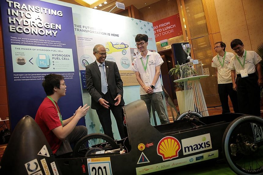 Minister for the Environment and Water Resources Masagos Zulkifli checking out a hydrogen fuel cell eco-car at Temasek Polytechnic's booth at the Ecosperity showcase yesterday. The minister announced the plan for a floating solar photovoltaic system