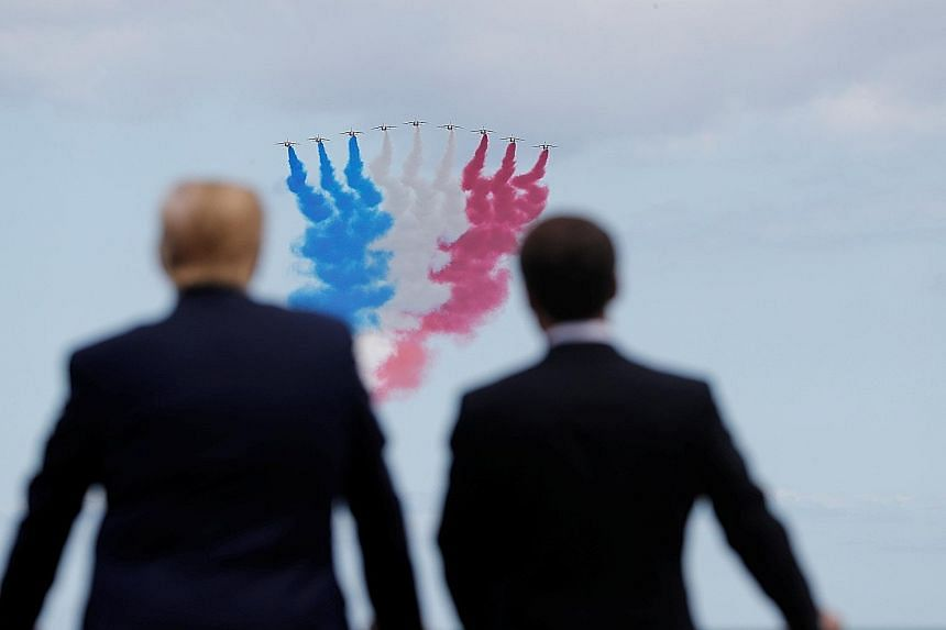 US President Donald Trump and French President Emmanuel Macron reviewing a flypast to commemorate the 75th anniversary of the D-Day landings at the Normandy American Cemetery in France yesterday. PHOTO: REUTERS