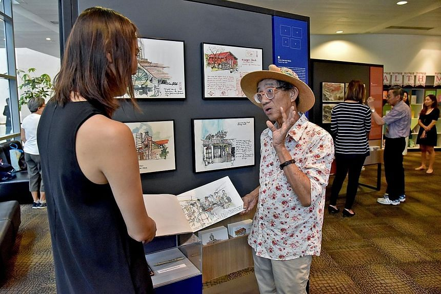 Mr Tony Chua speaking to a visitor about his sketches at Jurong Regional Library yesterday. He is one of three senior Singaporean artists whose pen and watercolour sketches are featured in a new exhibition called Uncles Love Monuments. ST PHOTO: JASM