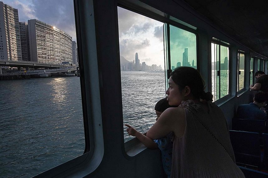 Passengers on a ferry looking at the Hong Kong skyline. Residential property values reached an all-time high last week after relentless gains over the past three months.