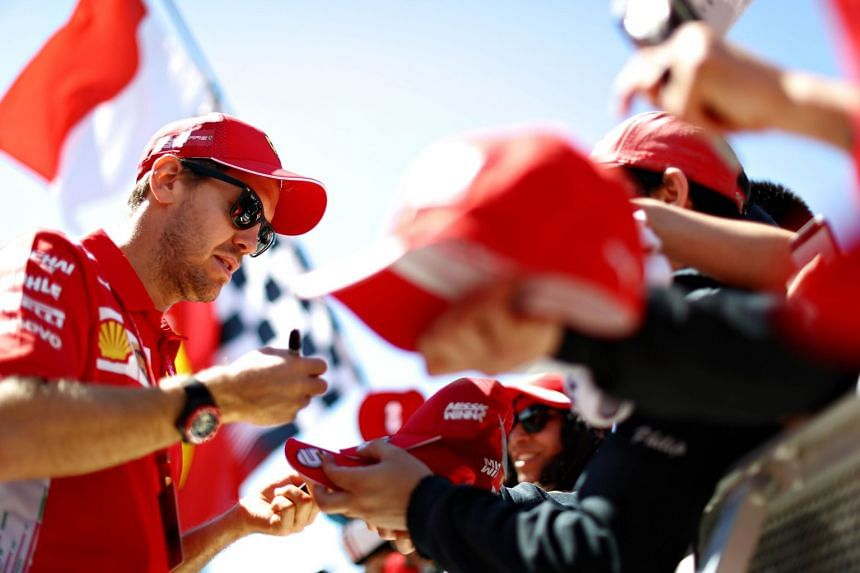 Sebastian Vettel signs autographs for fans during previews ahead of the Canadian Grand Prix.