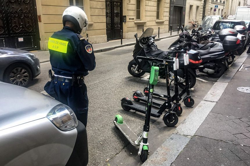 An official moves electric scooters from car parking spaces into those for motorcycles on a road in Paris.