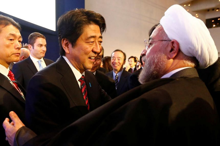 Japan's Prime Minister Shinzo Abe greets Iran's President Hassan Rouhani during the annual meeting of the World Economic Forum in Davos on Jan 22, 2014.