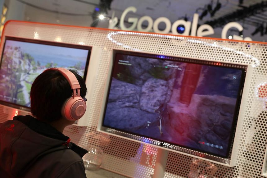 Attendees try out Google's Stadia at the Game Developers Conference in San Francisco, California.