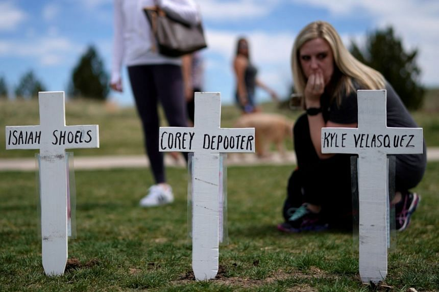 Attack survivor Cassanda Sadusky looks at a line of crosses commemorating those killed in the Columbine High School shooting.