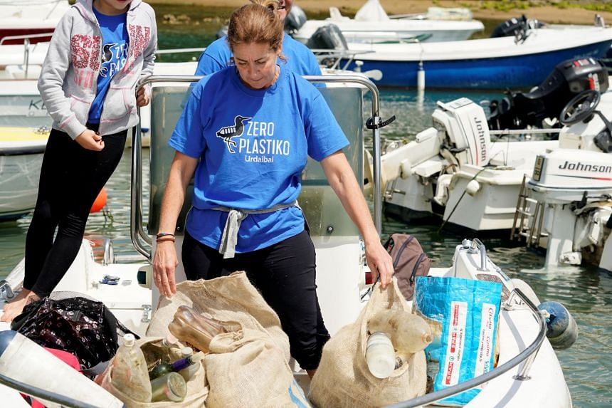 Volunteers load bags of plastic waste collected during the clean-up.