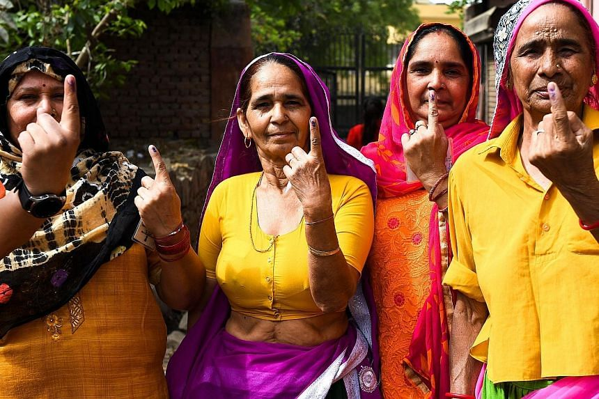 Women showing their ink-marked fingers after voting in last month's general election. Changing demographics has led to a vote in one part of India holding greater value than a vote in another part.