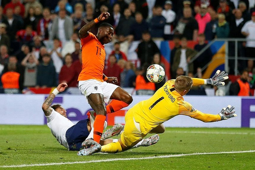 England's Kyle Walker scoring an own goal during extra time while under pressure from Dutch striker Quincy Promes during their Nations League semi-final match in Guimaraes on Thursday. The Netherlands won 3-1 to book a final meeting with Portugal tom