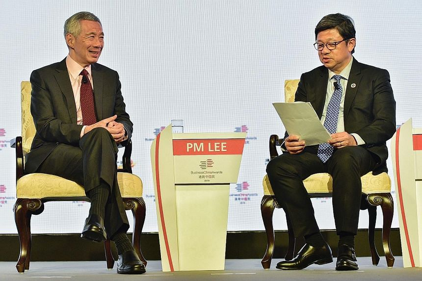Prime Minister Lee Hsien Loong at a dialogue during the Business China Awards gala dinner last night with Business China director Robin Hu, who moderated the dialogue. ST PHOTO: DESMOND WEE