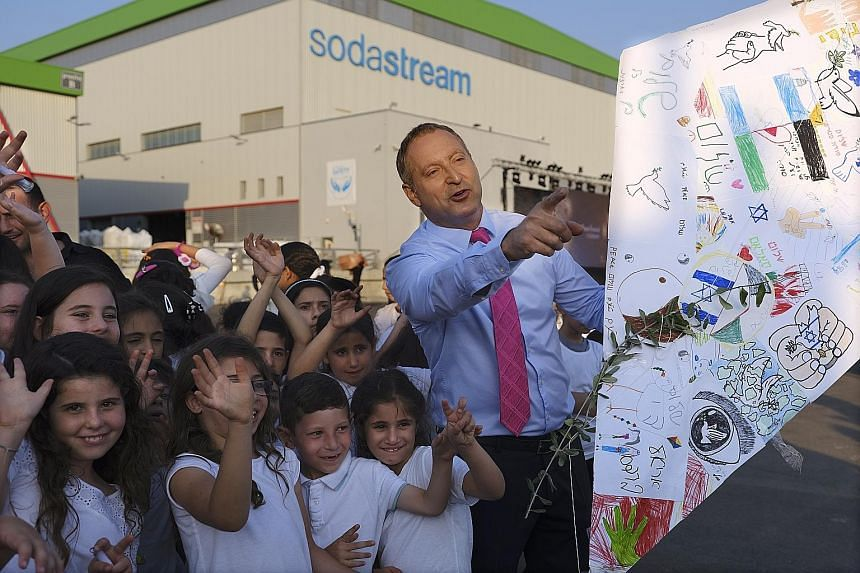 """SodaStream CEO Daniel Birnbaum flying """"peace kites"""" with Jewish and Muslim children outside the company factory near Rahat, Israel, last year."""