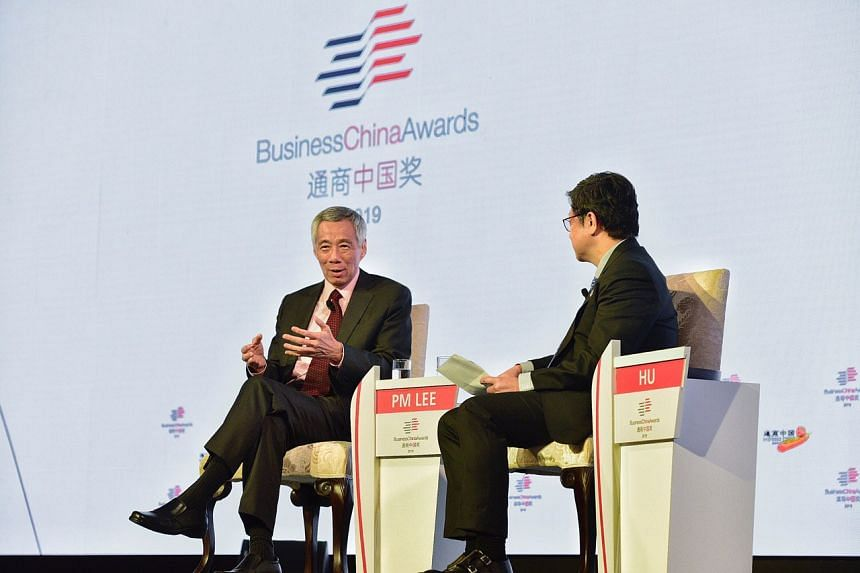 Prime Minister Lee Hsien Loong (left) gave his views on US-China relations and a range of other issues during the dialogue, moderated by Business China board director Robin Hu (right), that was held at Marina Bay Sands Expo and Convention Centre.