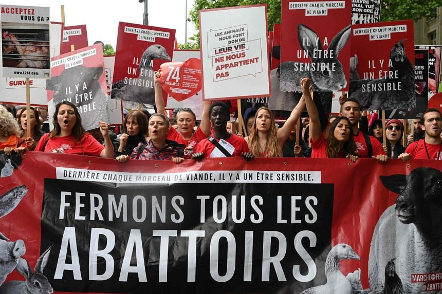 People hold a banner that reads, 'Close our abattoirs' during a demonstration in Paris.