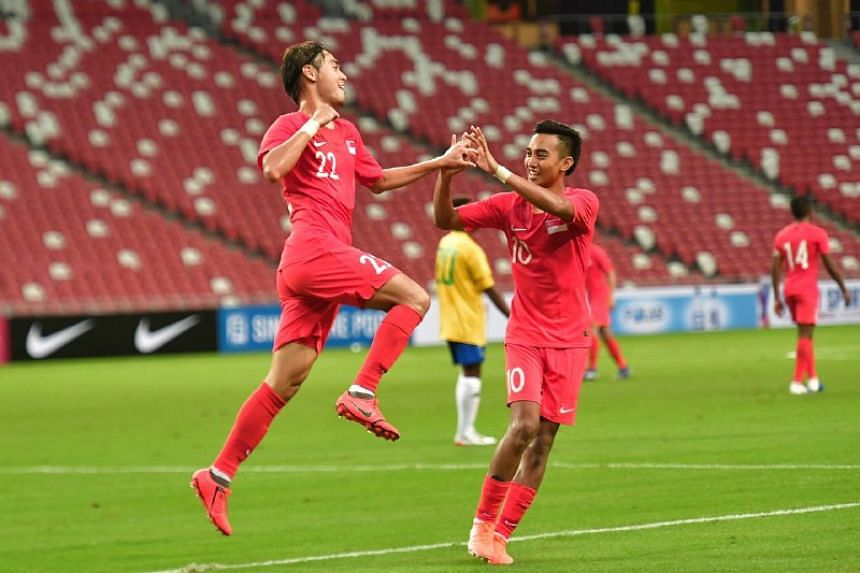 Singapore's Gabriel Quak celebrates with teammate Faris Ramli after scoring the Lions' third goal against the Solomon Islands in an international friendly at the National Stadium on June 8, 2019.