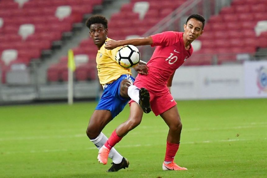Singapore's Faris Ramli and Solomon Islands' Michael Boso in action during their international friendly at the National Stadium on June 8, 2019.